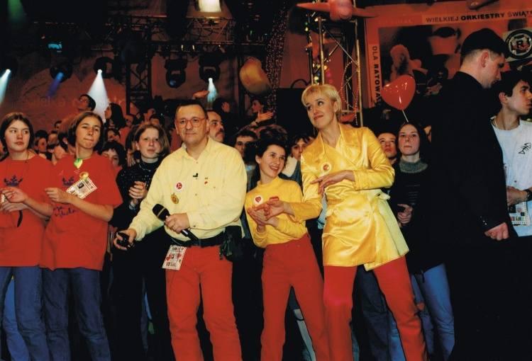Już pierwsze finały Wielkiej Orkiestry Świątecznej Pomocy wygenerowały tradycję, która trwa do dziś. Czerwone spodnie, żółta koszula i czerwone okulary Jurka Owsiaka to prawie jak mundurek jednej niedzieli w roku.<br /> <br /> Na zdjęciu jeden z pierwszych finałów WOŚP. Jurek Owsiak i Agata...