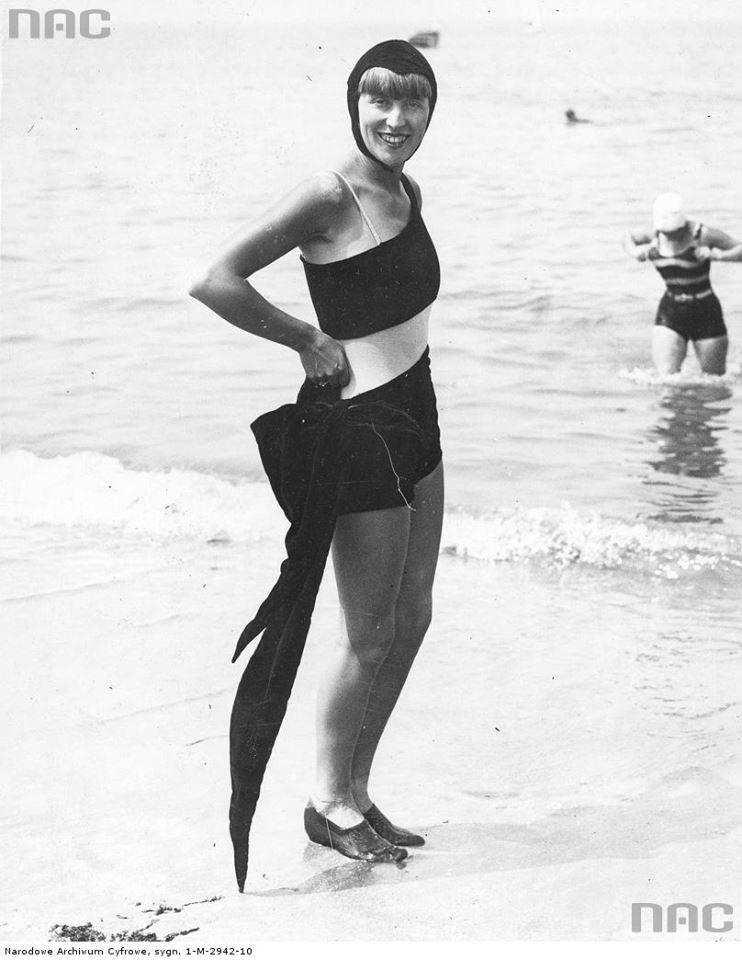 Kobieta na plaży w welwetowym kostiumie kąpielowym z kokardą u boku i czepku