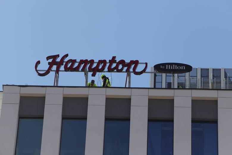 Na budynku przyszłego hotelu Hampton by Hilton pojawiło się już hotelowe logo.  Mimo epidemii koronawirusa prace przy budowie postępują.Budowa ma się