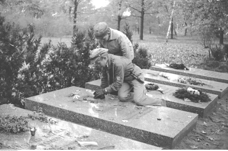 Harcerze zapalają znicze na grobie. Warszawa, Powązki, 1963-64 rok.
