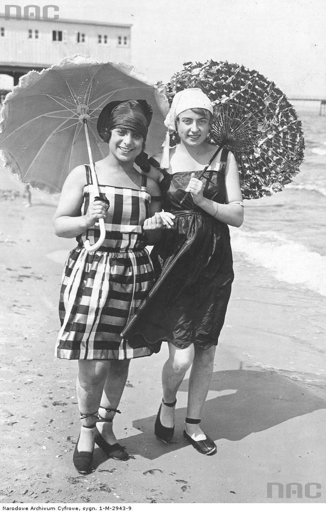 Kobiety w strojach kąpielowych i z parasolkami podczas spaceru nad Morzem Bałtyckim.