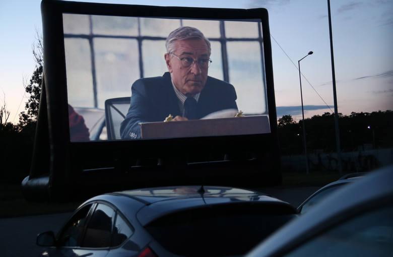 """Na parkingu Galerii Grudziądzkiej w sobotni wieczór z kina samochodowego skorzy stało kilkadziesiąt """"załóg"""" samochodowych i widzów"""