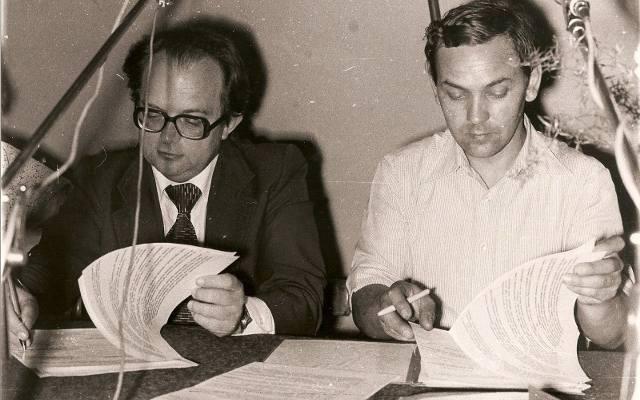 """Włodzimierz Pucek (pierwszy z prawej) jako uczestnik negocjacji w strajkującym """"Froteksie"""". Zdjęcie przedstawia prawdopodobnie moment podpisania porozumienia kończącego strajk."""