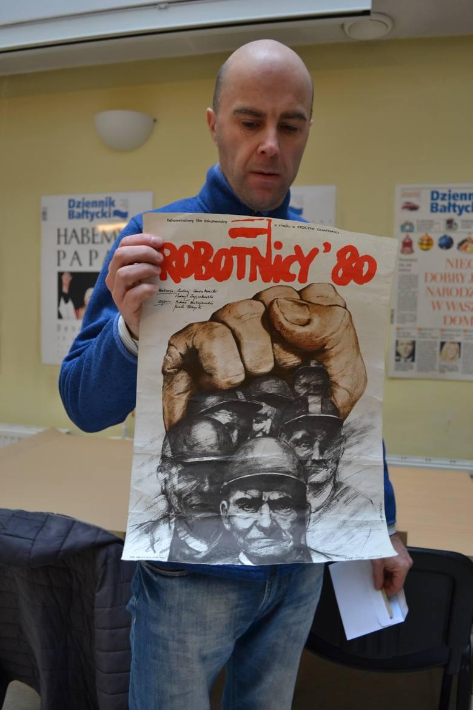 """Andrzej Moritz z plakatem do słynnego filmu """"Robotnicy '80"""""""