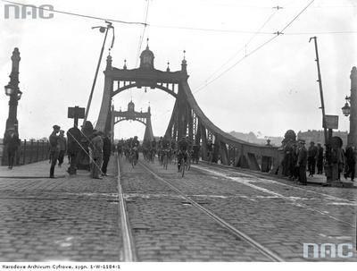 Patrol rowerzystów zjeżdża z Mostu Krakusa. W latach 1903-1913 wybudowano most Krakusa, łączący główną wtedy trasę na południe Krakowa. W latach 1968-1971