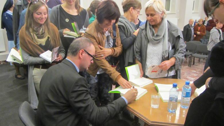 """Po spotkaniu w opolskim Duszpasterstwie Akademickim """"Xaverianum"""" ks. Jan Kaczkowski podpisywał swą najnowszą książkę."""