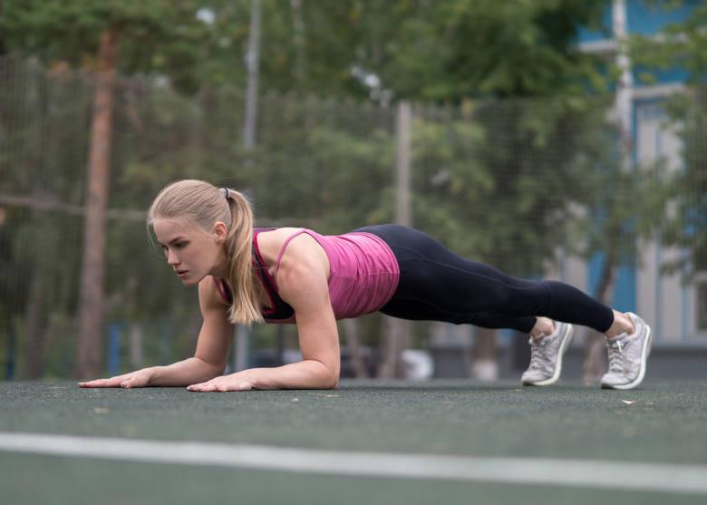 1. Połóż się na brzuchu, dłonie umieść dokładnie poniżej ramion. Ściągnij łopatki, wciągnij brzuch, maksymalnie napnij pośladki i ustaw miednicę tak,