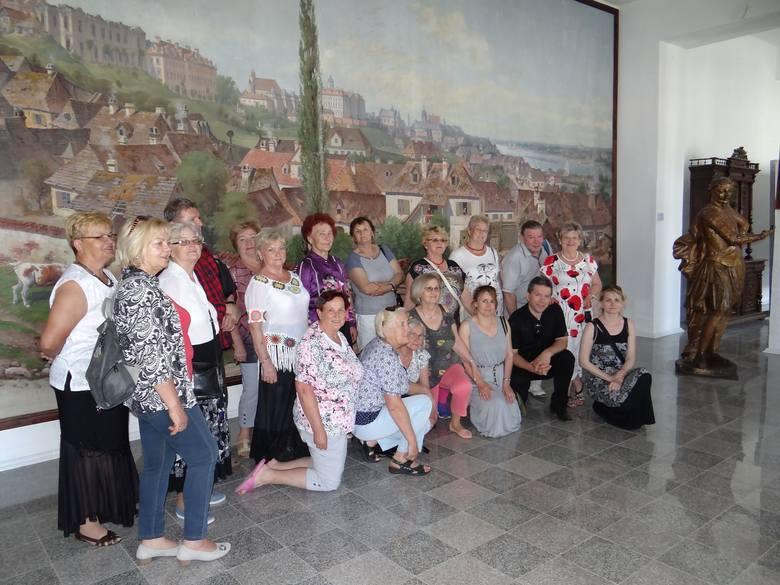 Grupa wycieczkowa na tle makiety Wiśniowca znajdująca się w pałacu