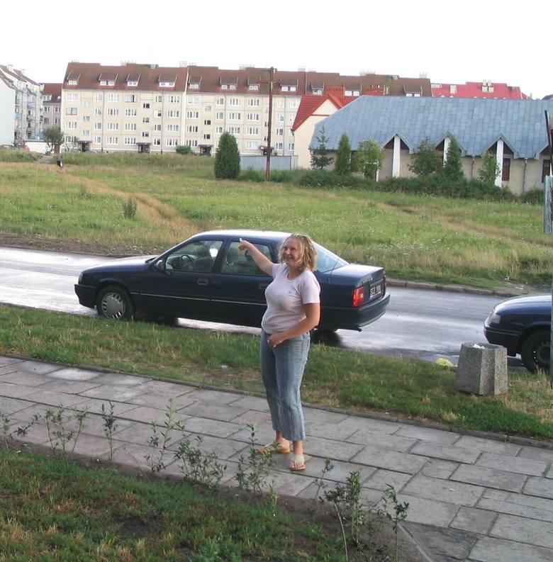 """Monika Jaworska z bloku nr 9 na ulicy Armii Krajowej pokazuje plac, na którym firma """"Parking"""" chce otworzyć płatny parking."""