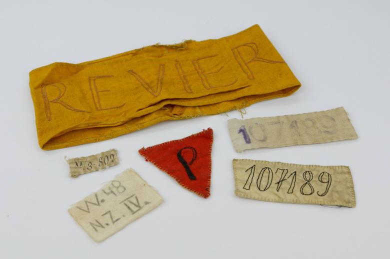 """Oznaczenia więźniarskie: numery, czerwony numer noszony przez więźniów politycznych i opaska z napisem po niemiecku """"revier""""."""
