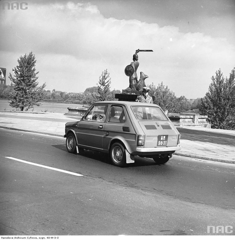 """Milicjantka zatrzymuje samochód Fiat 126p. W tle pomnik Syrenki i Wisła.  <font color=""""blue""""><a href="""" http://www.audiovis.nac.gov.pl/obraz/209141/9d80cd9f1dcd80df40434bc5eceb5bf7/""""><b>Zobacz zdjęcie w zbiorach NAC</b></a> </font>"""