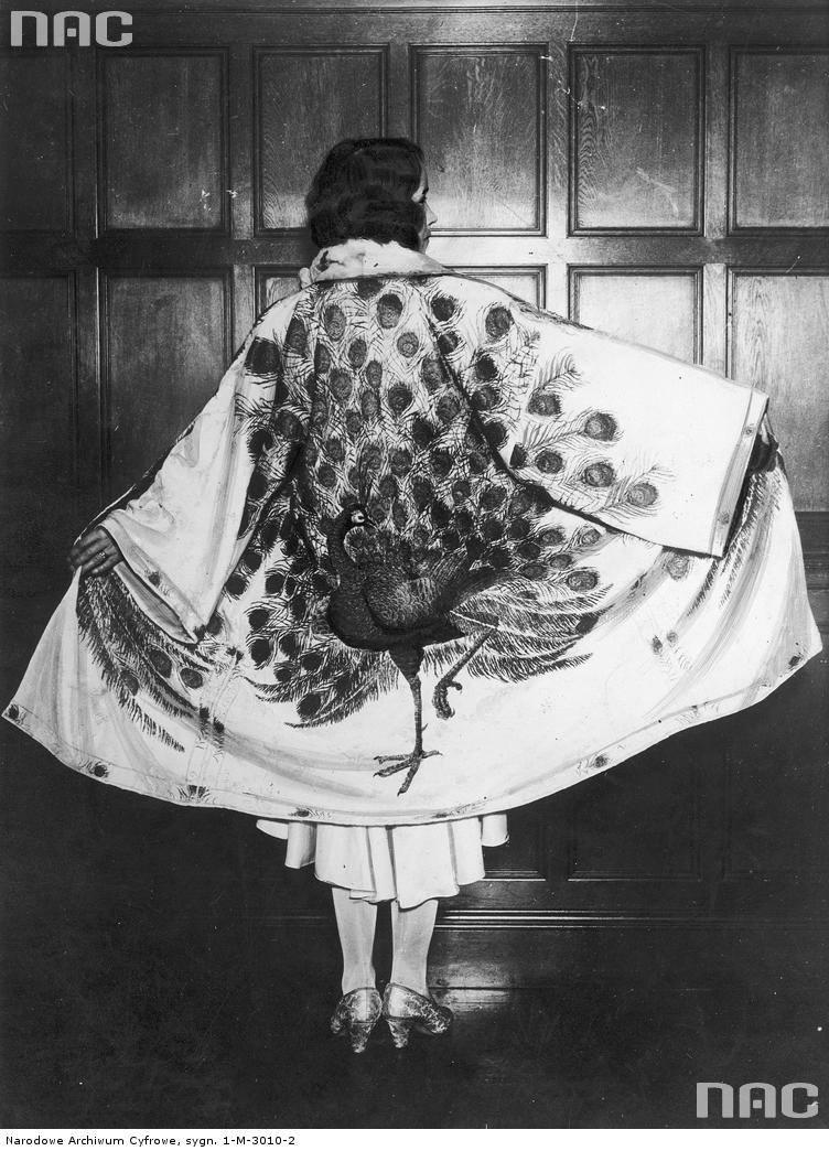 Modelka w stroju wieczorowym z peleryną z namalowanym bażantem przypominającą uniform chińskiego mandaryna.