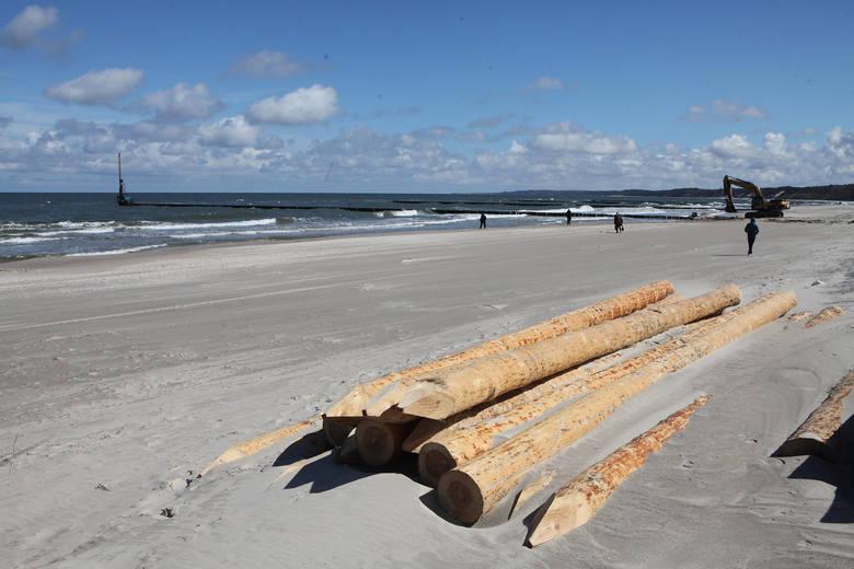 Na plaży wschodniej w Ustce trwają prace związane z odbudową uszkodzonych przez jesienne sztormy fragmentów palisady ostróg chroniących plażę przed efektami