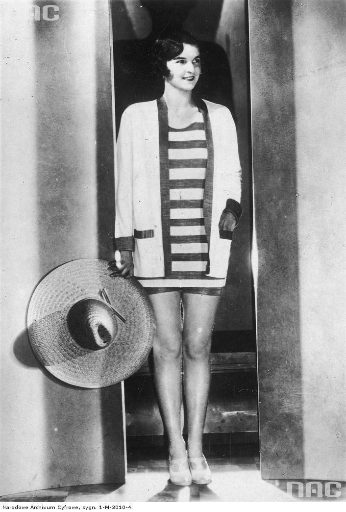 Modelka w kostiumie plażowym z trykotu. W ręku trzyma kapelusz słomkowy.