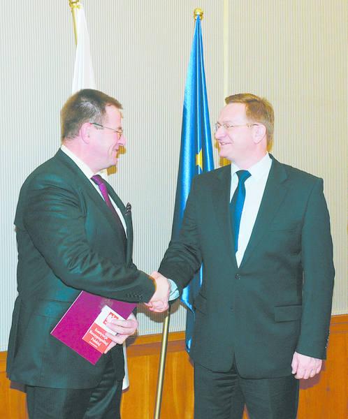 Ryszard Wilczyński gratuluje Siegmundowi Dransfeldowi. Wraz z aktem nadania obywatelstwa otrzymał on Konstytucję RP.