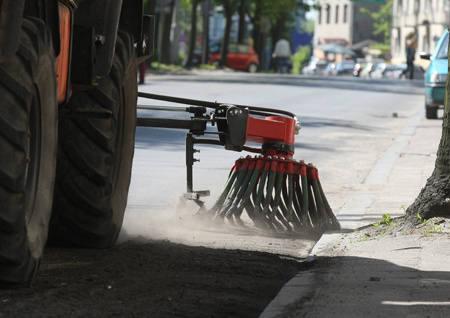 Maszyna bez trudu usuwa zalegający przy krawężniku piach