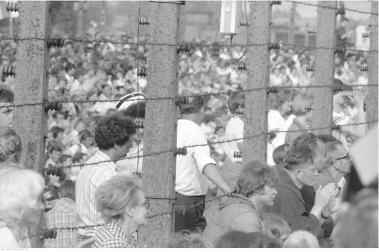 Pobyt papieża Jana Pawła II w Oświęcimiu-Brzezince podczas I pielgrzymki do Polski. Uczestnicy mszy św. odprawianej przez papieża Jana Pawła II na terenie byłego obozu Auschwitz II - Birkenau zgromadzeni przy ogrodzeniu obozu.<br /> Data wydarzenia: 1979-06-07