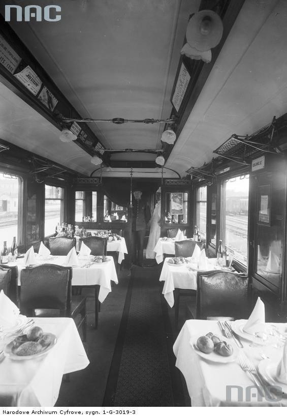 Przykryte obrusami stoły, zastawa stołowa, sztućce, pieczywo i alkohol w wagonie restauracyjnym