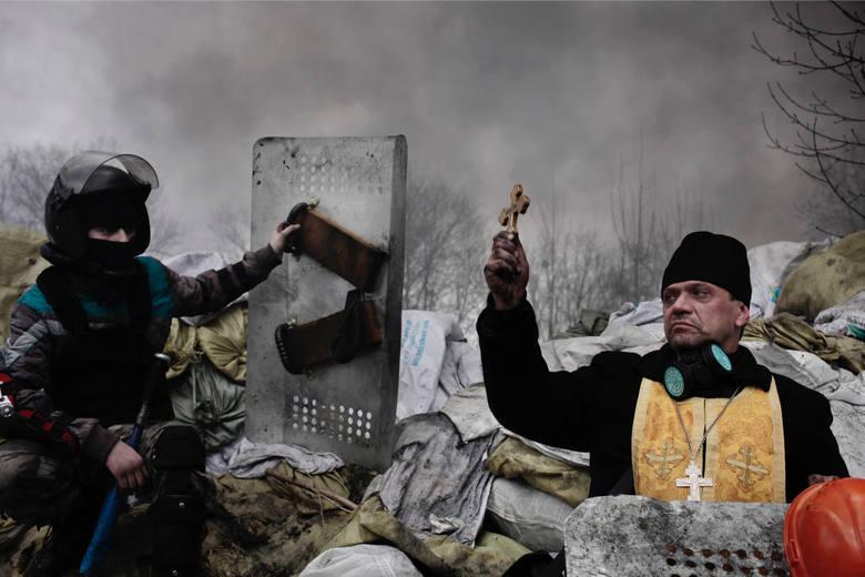 """WORLD PRESS PHOTO 2015. Drugie miejsce w kategorii """"News - fotoreportaż"""". Prawosławny duchowny błogosławi uczestnika protestów w Kijowie."""