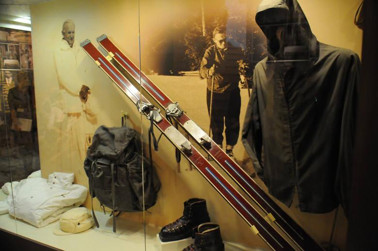 Sprzęt narciarski Wojtyły. Są tu: kurtka, plecak, narty, kijki, wosk oraz buty narciarskie