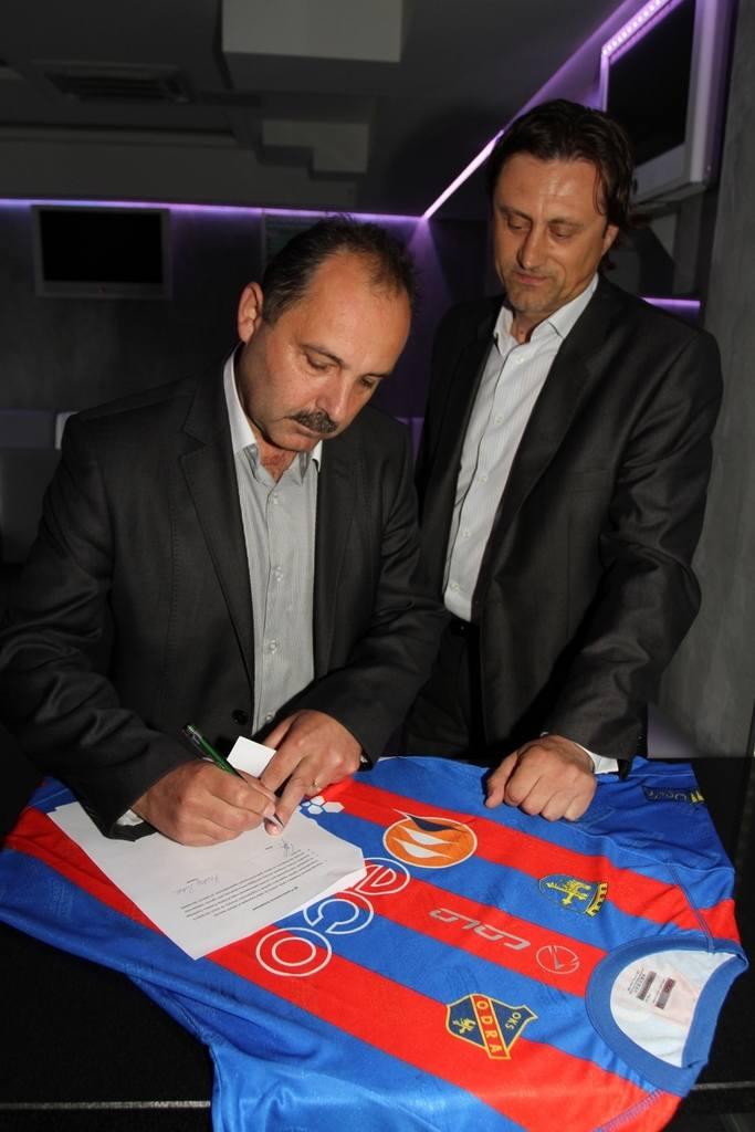Wiceprezes Odry Ireneusz Gitlar (z lewej) i trener Andrzej Polak podpisują umowę.