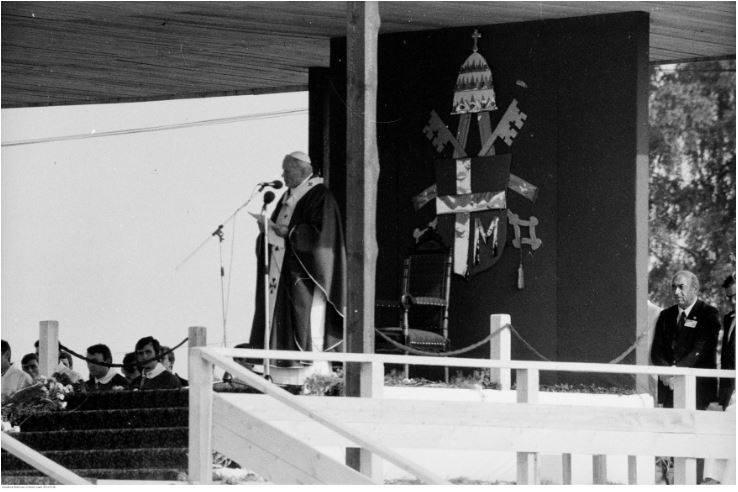 Pobyt papieża Jana Pawła II w Oświęcimiu-Brzezince podczas I pielgrzymki do Polski. Papież Jan Paweł II przemawia podczas mszy św. odprawianej na terenie byłego obozu koncentracyjnego Auschwitz II - Birkenau. Z prawej widoczny sekretarz papieża, ks. Stanisław Dziwisz. W dekoracji ołtarza widoczny...