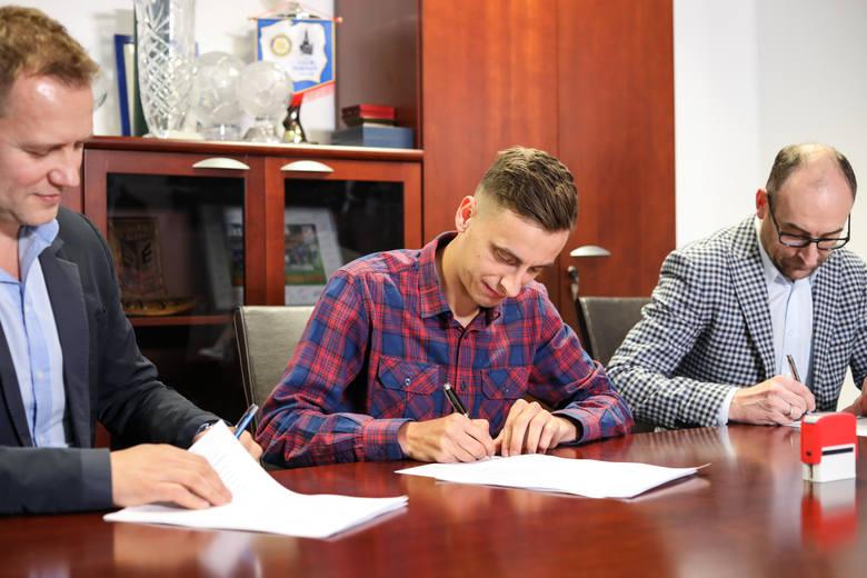 Juliusz Letniowski składa podpis na kontrakcie z Lechem w obecności dyrektora sportowego Tomasza Rząsy i prezesa Karola Klimczaka