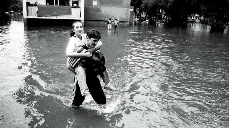 Opole 1997. Ulica Prószkowska. Mężczyzna niesie kobietę do wojskowej ciężarówki. Pojazd pełnił rolę taksówki, wożąc ludzi z mokrej do suchej części miasta.