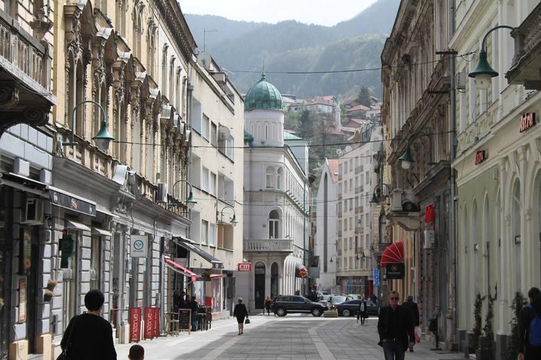 Sarajewo, widok sprzed katedry katolickiej. Wokół kamienice, pamiętające czasy cesarza Franciszka Józefa, w tle minaret meczetu. Dachy i góry.