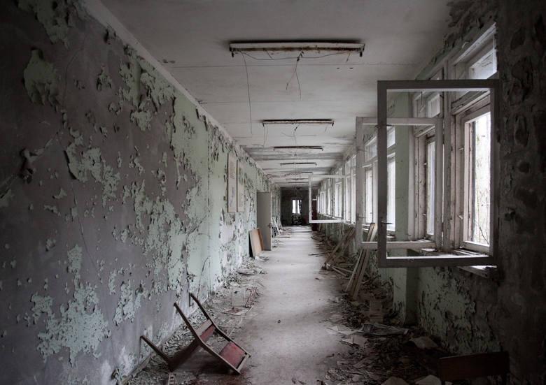 Budynek szkoły w Prypeci. Porozrzucane krzesła, książki, deski. J. Niemczyk: -I ta odpadająca farba ze ścian. Fascynująca