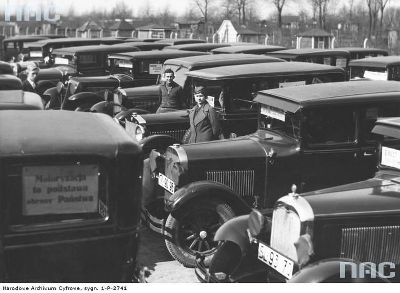 """Grupa właścicieli taksówek przy pojazdach. Po lewej widoczna tabliczka lub karta przymocowana na szybie samochodu z hasłem: """"Motoryzacja to podstawa obrony Państwa"""".  <font color=""""blue""""><a href=""""http://www.audiovis.nac.gov.pl/obraz/137305/85808006418460f1a0bae7b08ea9ad85/""""><b>Zobacz zdjęcie w..."""