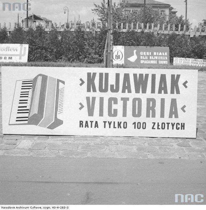 Baner reklamowy akordeonów Kujawiak i Victoria produkcji Bydgoskiej Fabryki Akordeonów na trasie Wyścigu Pokoju