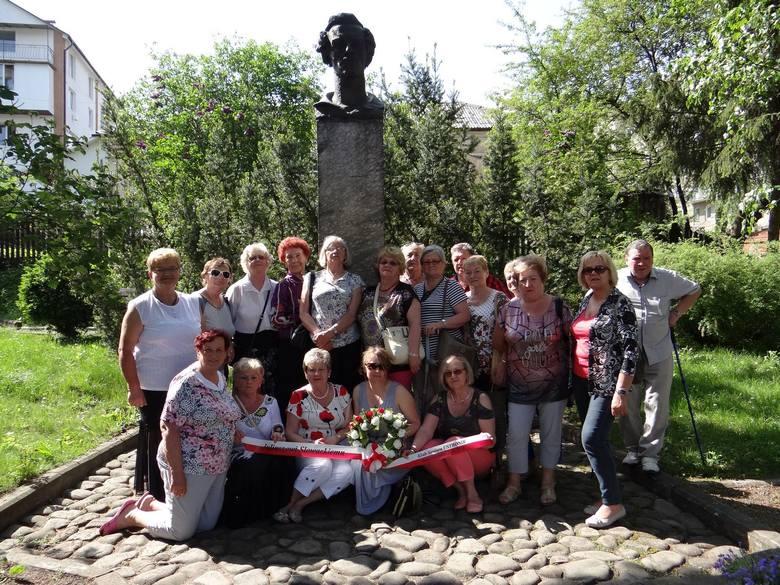 Wycieczkowicze na tle pomnika Juliusza Słowackiego, znajdującego się na terenie dworku w Krzemieńcu, gdzie mieszkał