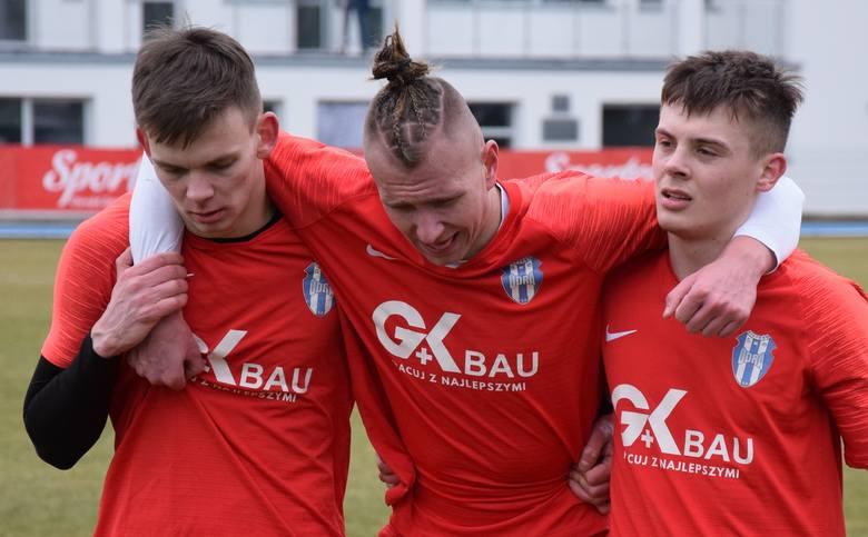 Dawid Leoszko z Odry Nietków, podtrzymywany przez kolegów z zespołu, schodzi z boiska po urazie kolana