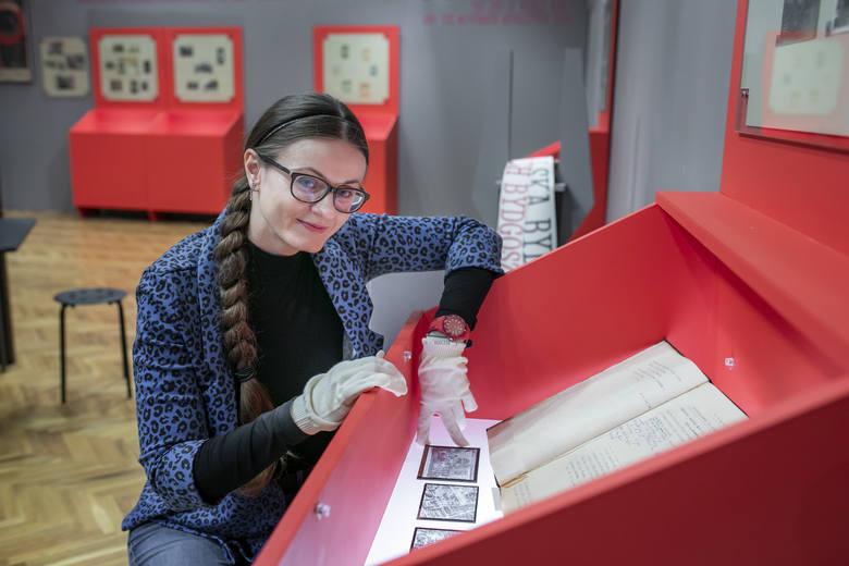 """Anna Nadolska, kuratorka wystawy """"Ku Wolności. Bydgoszcz 1914-1920"""", przy specjalnie podświetlanych gablotach, w których prezentowane są unikatowe szklane"""