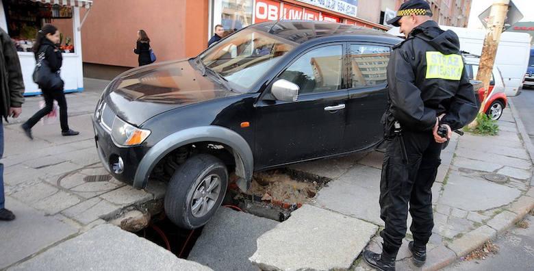 Samochód wpadł w dziurę po studzience.