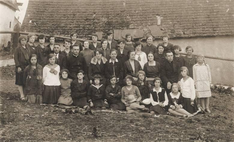 Maria Wojciechowska (siedzi obok księdza, w płaszczu z futrzanym kołnierzem) w towarzystwie grona pedagogicznego i uczniów