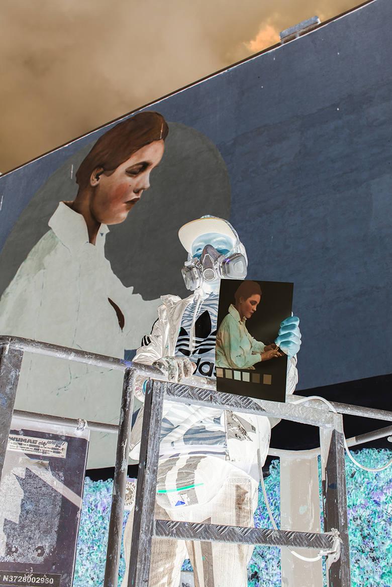 Zdjęcie zrobione w negatywie sprawia, że mural, jak i projekt trzymany w ręku przez artystę, są widoczne w pozytywie