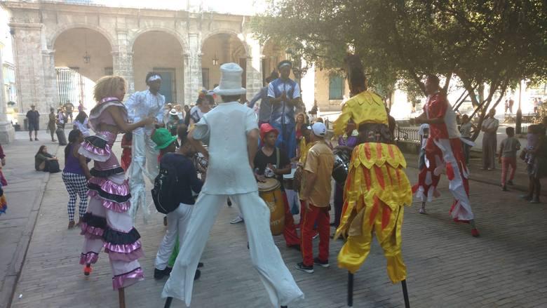 Muzycy i szczudlarze w kolorowych strojach przechodzą ulicami między placami ku uciesze turystów