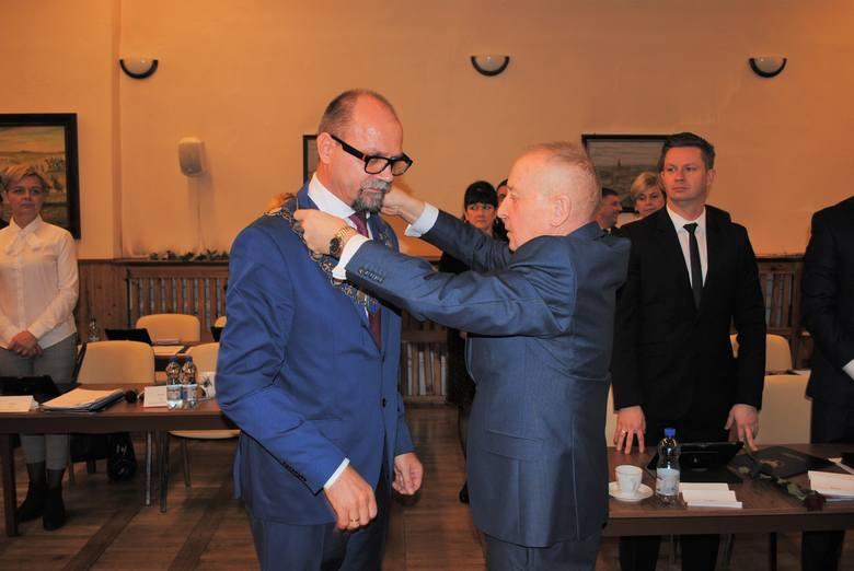 Henryk Borowicz, radny senior zakłada radnemu Stanisławowi Gliszczyńskiemu łańcuch - insygnia władzy przewodniczącego