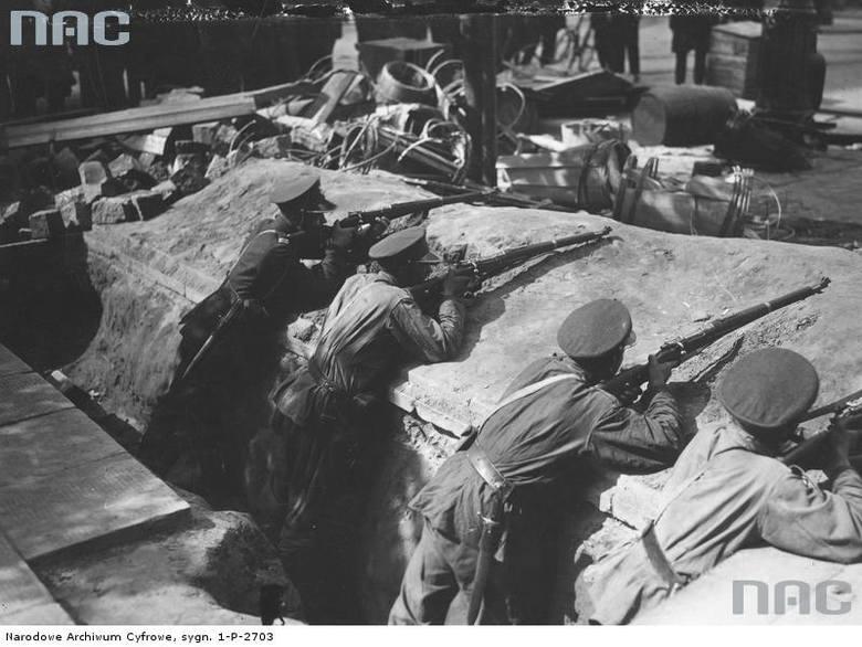 Szwoleżerowie podczas strzelania z karabinów w okopach na jednej z ulic Warszawy.