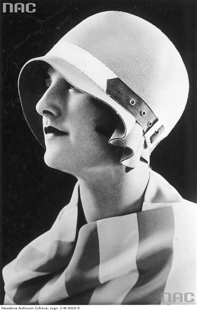 Modelka w białym filcowym kapelusiku ozdobionym skórzanym paskiem zapinanym na sprzączkę.