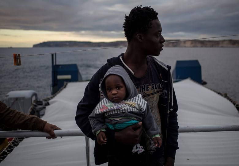 Migrant trzymający dziecko na pokładzie statku Sea Watch 3