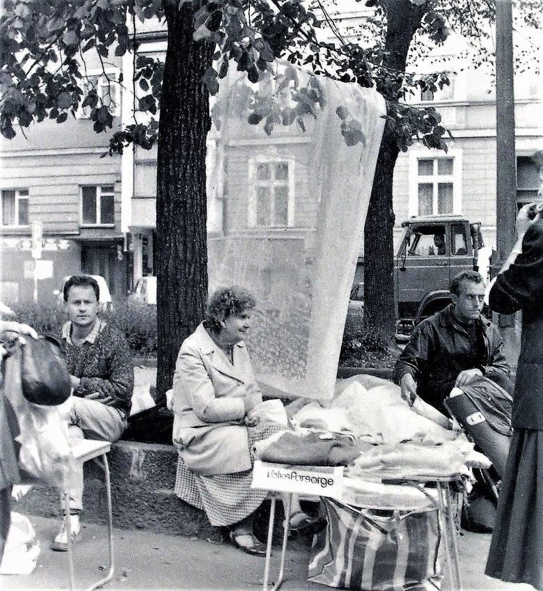 Uliczne stragany z firanami eksponowanymi na drzewach deptaku al. Wojska Polskiego wczesną jesienią 1990 roku