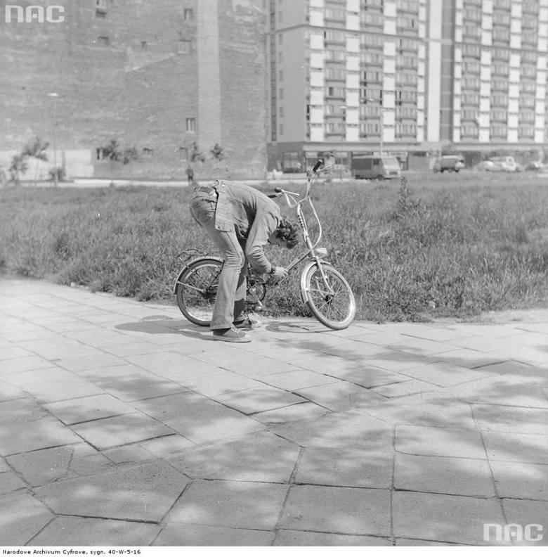 Mężczyzna naprawiający rower składany Sokół-Lux. W tle przedwojenna kamienica oraz jeden z bloków mieszkalnych Osiedla Za Żelazną Bramą