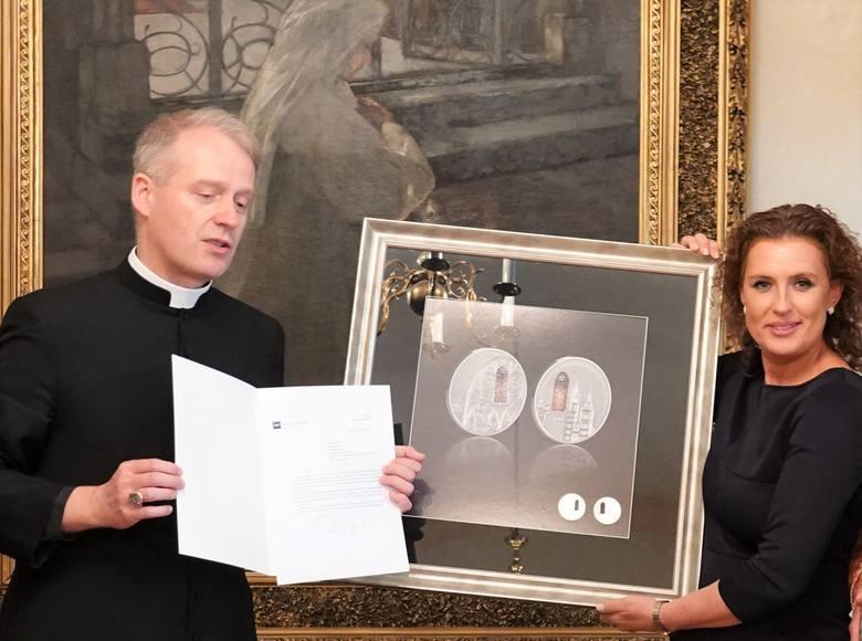 Przekazanie monet archiprezbiterowi Bazyliki Mariackiej ks. infułatowi Dariuszowi Rasiowi przez dyrektor oddziału okręgowego NBP w Krakowie Katarzynę