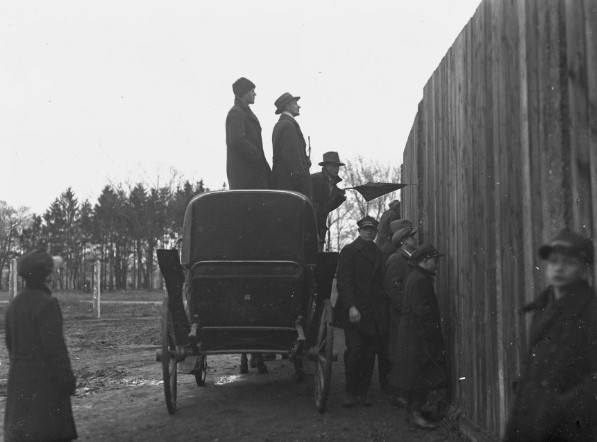 To płot przy stadionie Wisły. Kibice w dorożce ustawionej przed ogrodzeniem i przez dziury w ogrodzeniu oglądają mecz Wisła - Garbarnia. Kwiecień 1930