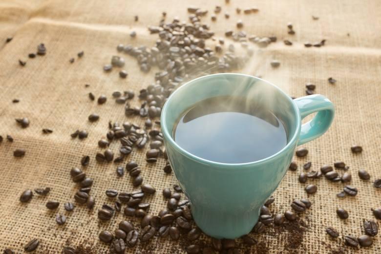 Błękitny kubek z kawą położony na jutowym nakryciu. Wokół leżą rozsypane ziarnka kawy.