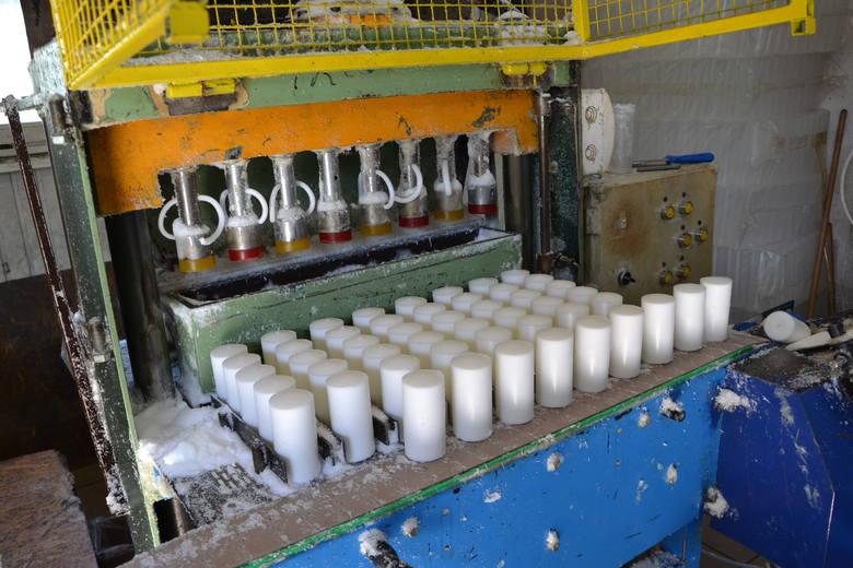 Specjalna maszyna najpierw odmierza odpowiednie porcje granulatu parafinowego, a następnie formuje wkłady do zniczy w kształcie walca.