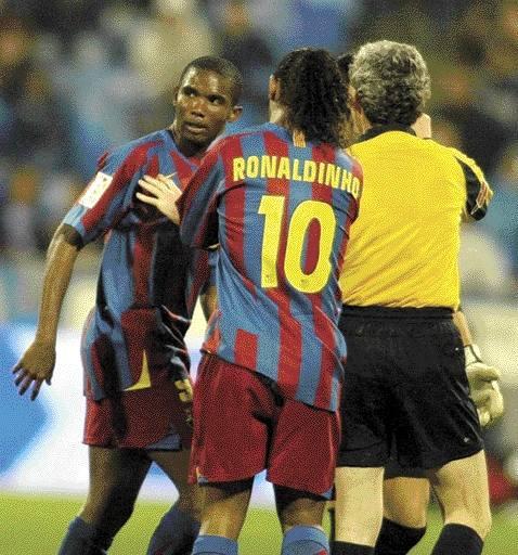 Samuel Eto`o (z lewej) powstrzymywany przez Ronaldinho i arbitra.
